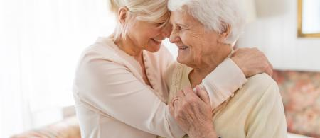 Elderly woman and daughter smiling and embracing with foreheads touching.
