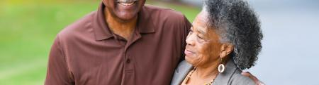 Two older adults smile and walk outside