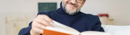 Man with glasses and a beard reading a book with an orange cover.