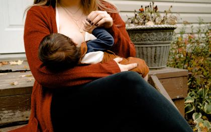 A woman sits outside breastfeeding an infant