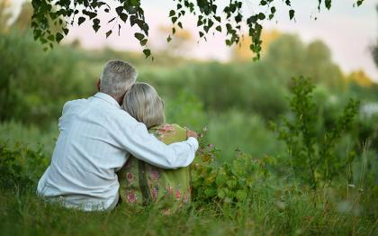 Older couple sitting under a tree in grassy field