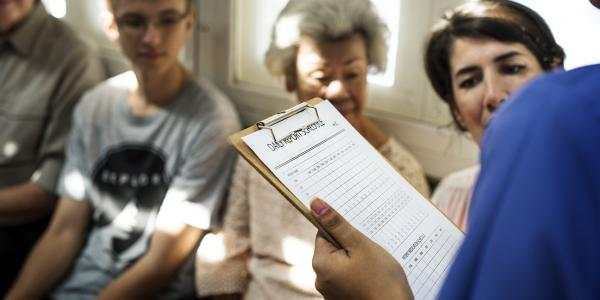 Healthcare provider holding clip board in crowded waiting room