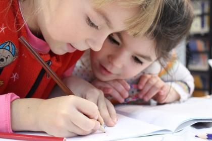Two children leaning over a workbook