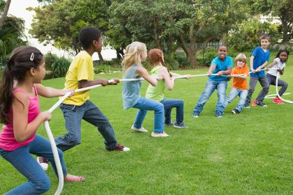 Group of kids play tug of war in a park