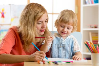 Childcare worker using colored pencils with toddler
