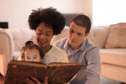 Two adults read with a young child