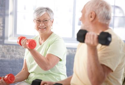 An older couple using weights to workout