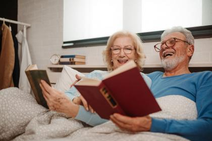 An older couple reading books in bed