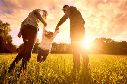 Two adults play with a toddler in a field near sunset