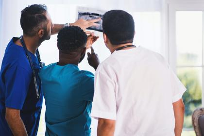 Adults in a medical setting looking at an x-ray