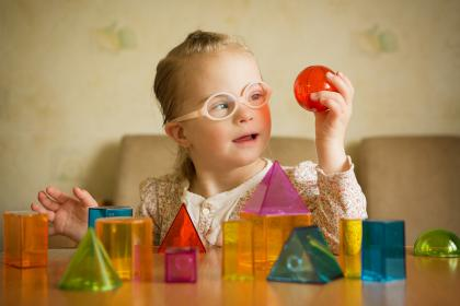 Young girl playing with colored shaped blocks