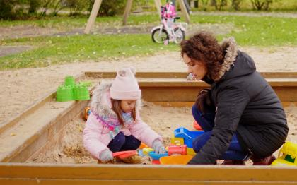 Mother playing with daughter in sandbox
