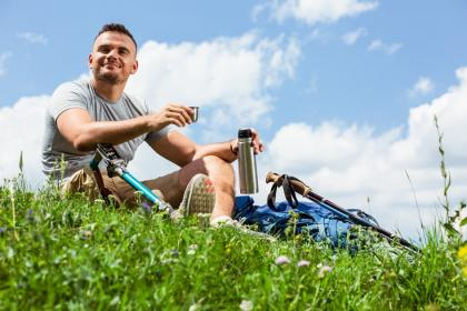 Young man with a prosthetic leg on a grassy knoll with his bicycle laying next to him.