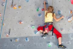 Young girl climbing indoor rock wall